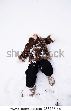 photo of Happy child baby girl in snow outdoors in winter