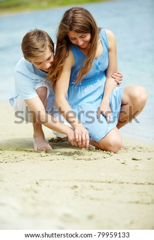 Photo of happy couple drawing heart on sand during summer vacation - stock photo