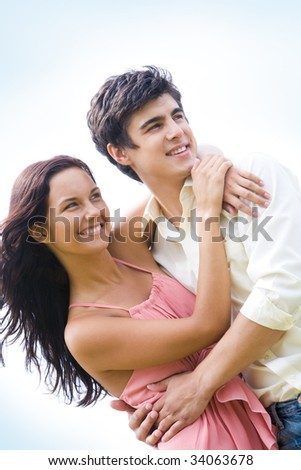 Photo of happy couple embracing each other and looking aside - stock photo