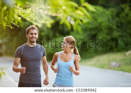 Photo of happy couple jogging on summer morning - stock photo