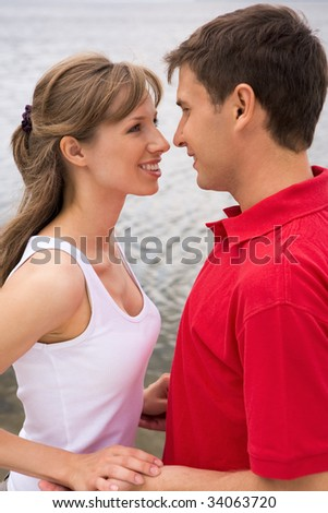 Photo of happy couple looking at each other with love outdoors - stock photo
