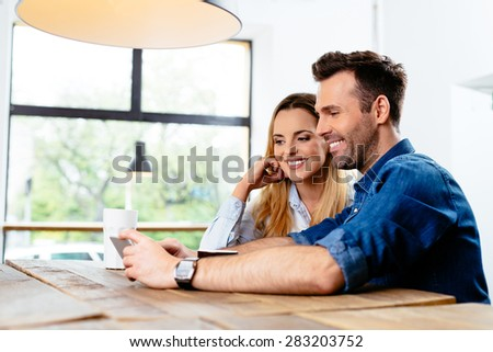 Photo of happy couple looking at smartphone at cafe - stock photo