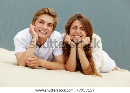 Photo of happy couple lying on sand and looking at camera