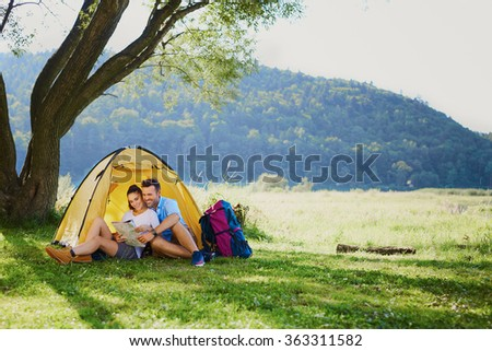 Photo of happy couple sitting in tent during hiking trip - stock photo