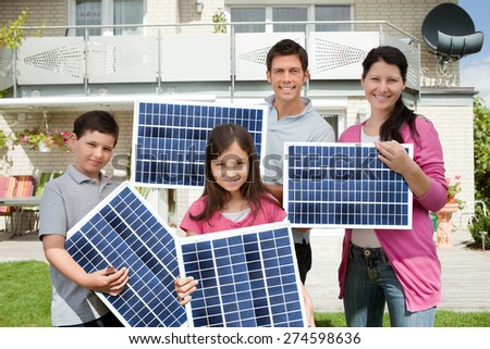 Photo Of Happy Family Carrying Solar Panels - stock photo