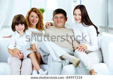 Photo of happy family looking at camera at home - stock photo