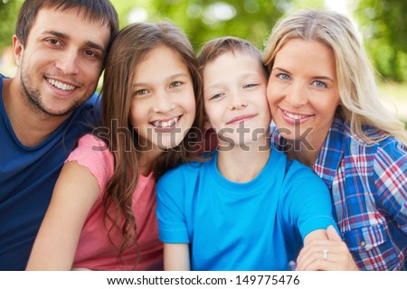 Photo of happy family of four looking at camera outdoors - stock photo
