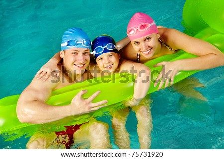 Photo of happy family of swimmers smiling at camera
