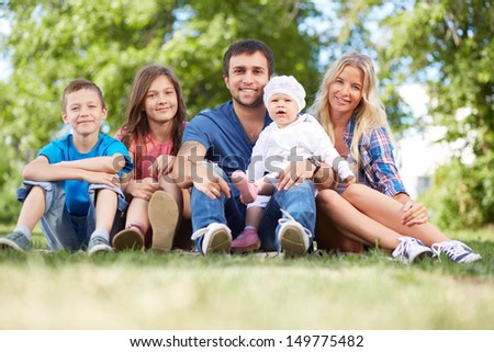 Photo of happy family sitting on grass during summer rest - stock photo