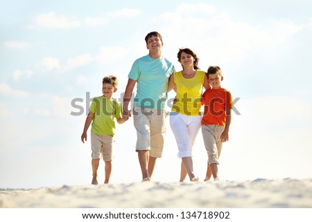 Photo of happy family walking down the beach on summer - stock photo