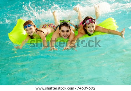 Photo of happy friends swimming in pool - stock photo