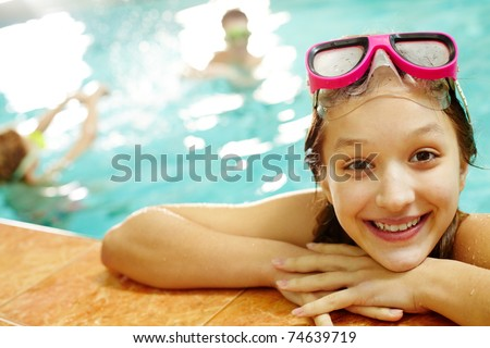 Photo of happy girl in pool smiling at camera - stock photo