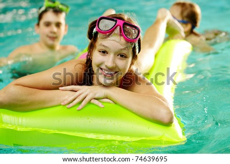Photo of happy girl in pool with her friends on background