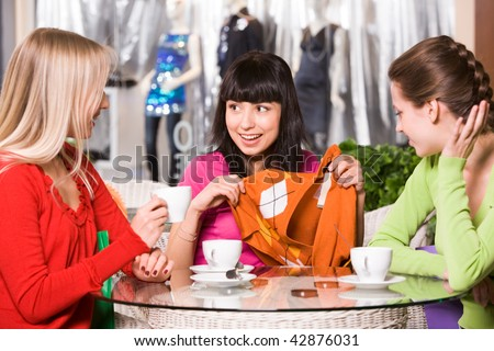 Photo of happy girl showing fashionable pullover to her friends in cafe