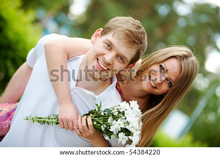 Photo of happy girl with bunch of white chrysanthemums embracing handsome male