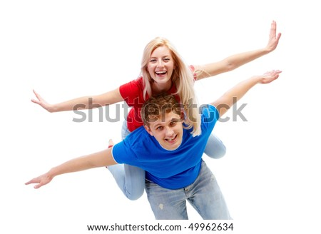 Photo of happy guy giving piggyback to joyful girl while both looking at camera - stock photo