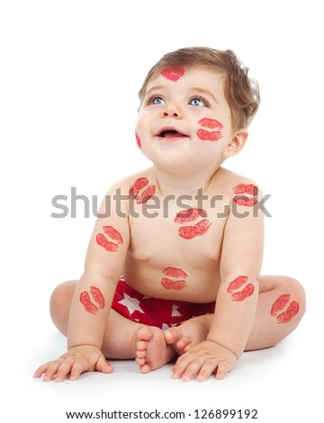 Photo of happy kid covered with red kisses print on the body, adorable baby boy sitting in studio isolated on white background, nice toddler looking up, Valentine day, love concept - stock photo