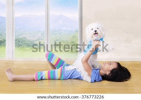 Photo of happy little girl with casual clothes holding her puppy at the home - stock photo