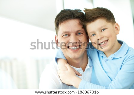 Photo of happy man and his son looking at camera with smiles - stock photo