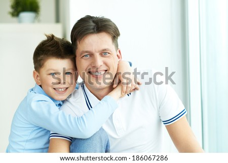 Photo of happy man and his son looking at camera with smiles while boy embracing his father - stock photo