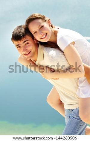 Photo of happy man giving piggyback to his girlfriend and having fun - stock photo