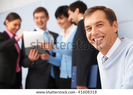 Photo of happy man looking at camera in working environment