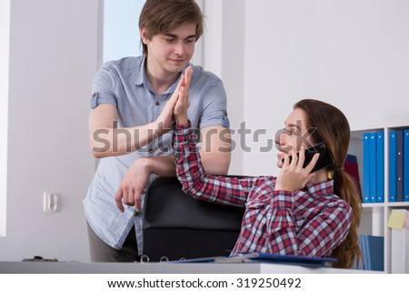 Photo of happy office workers making high five - stock photo