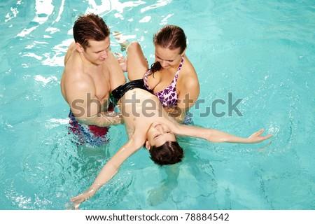 Photo of happy parents teaching their son how to swim - stock photo