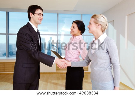 Photo of happy partners handshaking after signing contract in office