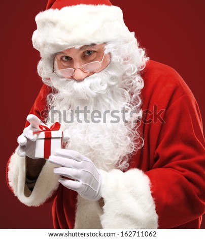 Photo of happy Santa Claus looking into white giftbox in isolation