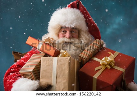 Photo of happy Santa Claus outdoors in snowfall carrying gifts to children - stock photo