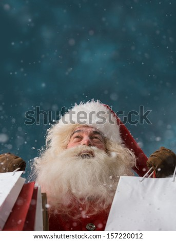 Photo of happy Santa Claus outdoors in snowfall holding shopping bags and looking upwards on big copyspace. Christmas sales and discount concept - stock photo