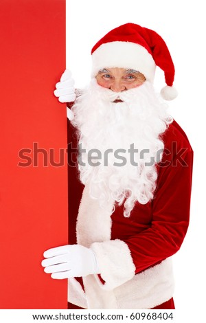Photo of happy Santa Claus peeking out of red billboard - stock photo