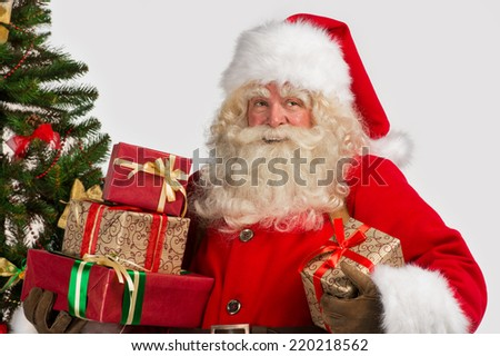 Photo of happy Santa Claus with giftboxes looking away - stock photo