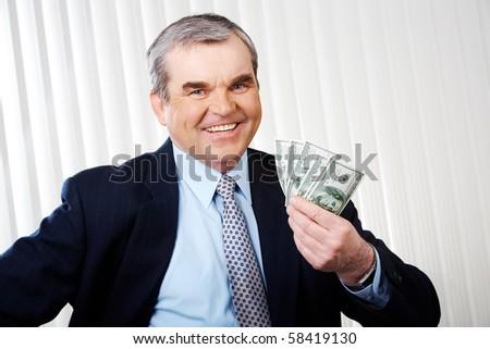 Photo of happy senior businessman with dollar banknotes - stock photo