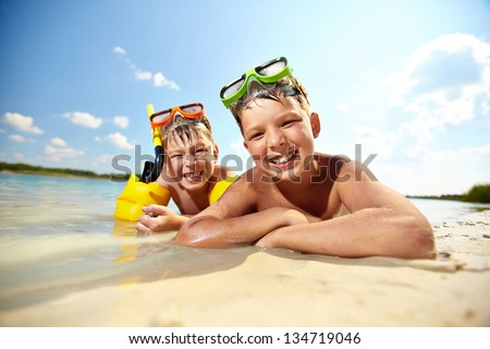 Photo of happy siblings lying on sand on summer vacation - stock photo