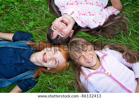 Photo of happy three girls lying on green grass laughing at camera - stock photo