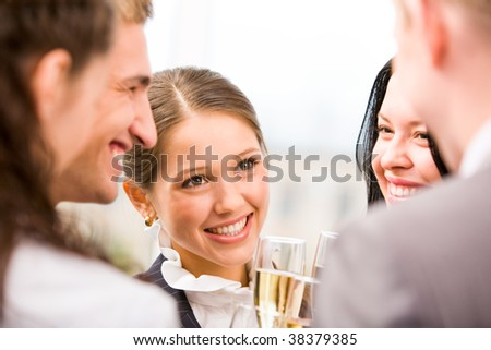 Photo of happy woman holding flute with champagne and smiling at her colleagues during party