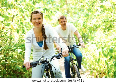 Photo of happy woman riding bicycle outdoors with her husband on background - stock photo