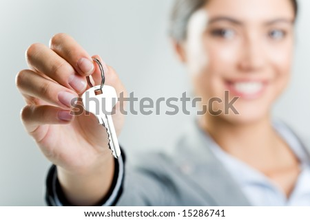 Photo of happy womanâ??s hand holding new key and pointing it at camera - stock photo