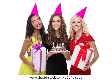 Photo of happy women looking at camera. They wearing birthday hats and holding  presents. One of them holding cake with candles. They are isolated on white background. Concept for happy birthday