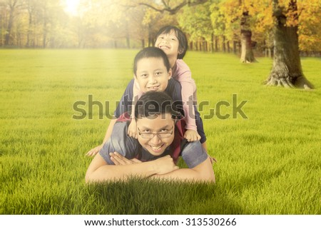 Photo of happy young father playing on the autumn park with his children while enjoying holiday - stock photo