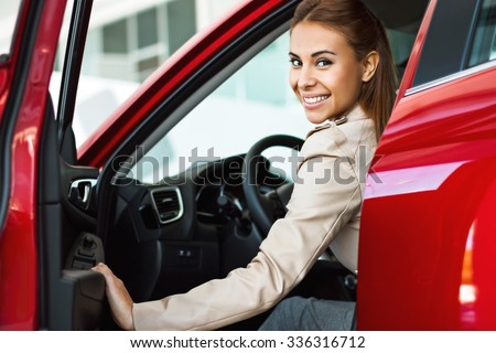 Photo of happy young mixed race woman sitting inside her new car. Concept for car rental - stock photo