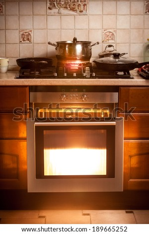 Photo of hot oven and pan boiling on stove at kitchen - stock photo