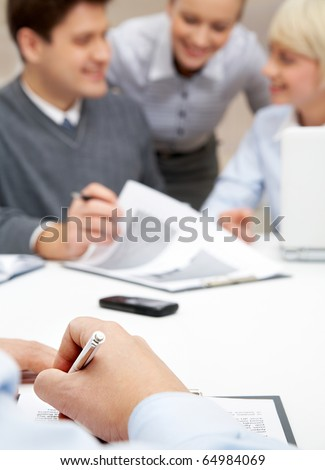 Photo of human hands making notes on background of man explaining idea to employees