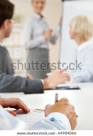 Photo of human hands over workplace on background of smart teacher explaining idea by the board