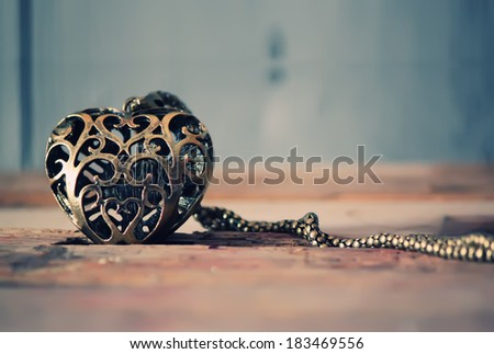 Photo of iron heart on wooden background - stock photo
