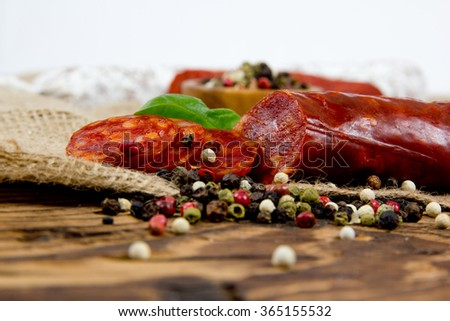 Photo of italian salami with herbs and spice on wooden board - stock photo