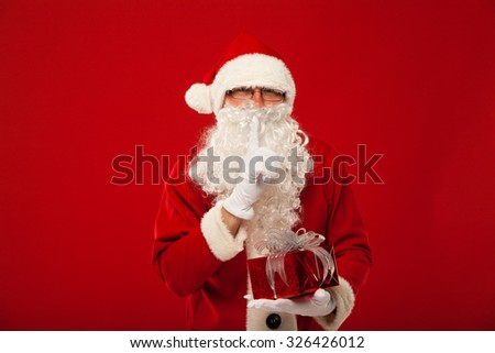 Photo of kind Santa Claus giving xmas present and looking at camera. secret hand and lips