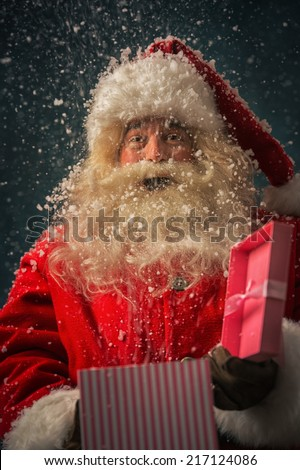 Photo of kind Santa Claus opening and giving xmas present to camera under snowfall - stock photo